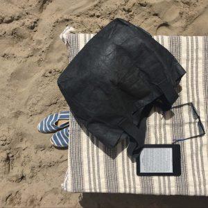 Sole, mare, ebook reader pieno di libri e borsa Essential